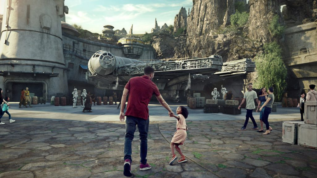 little girl excitedly pulling her father's hand to drag him into Star Wars: Galaxy's Edge area