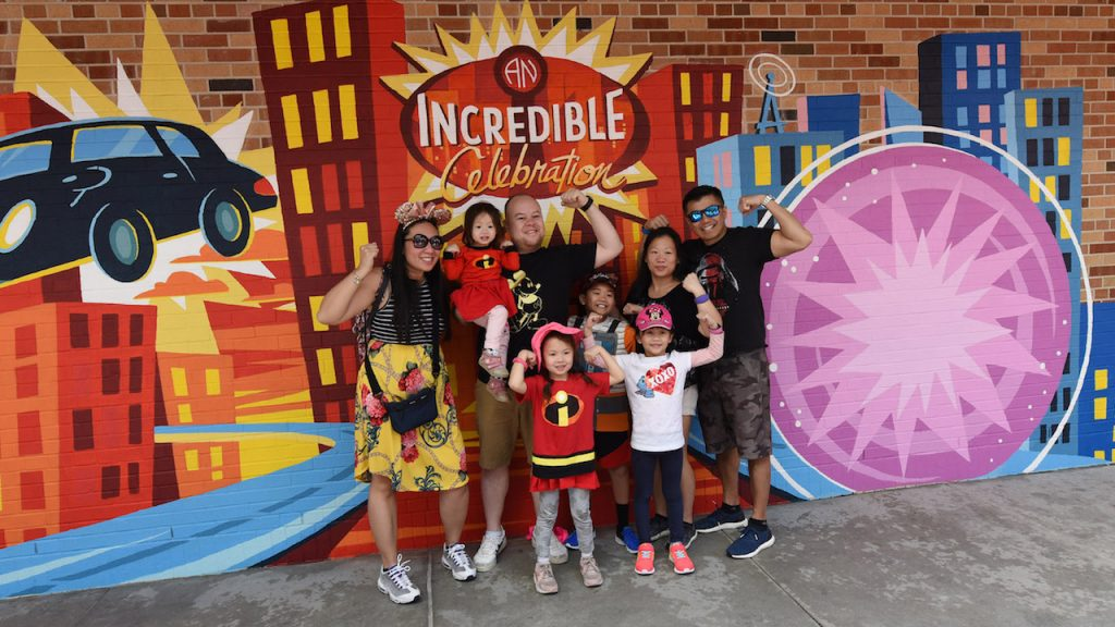 Famiy posing in front of new Incredibles Celebration Background