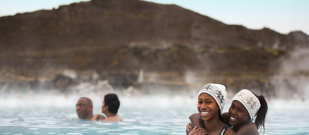 Two girls in matching headbands wade in an outdoor bath of steaming water near a man and a woman with a mountain in the background