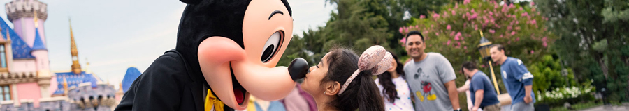 A young girl greets Mickey in front of Sleeping Beauty Castle by kissing him on the nose as he shakes her hands