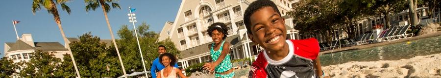 Un garçon souriant fait des éclaboussures avec de l'eau jusqu'aux genoux alors que sa famille le regarde en arrière-plan