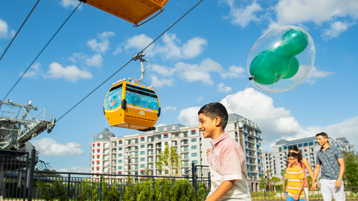 A father and son stroll beneath a Disney Skyliner gondola